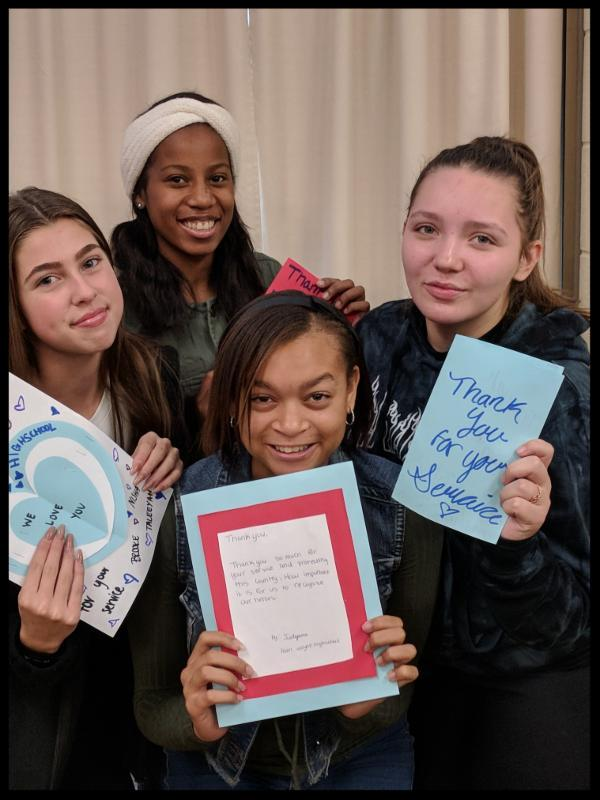Four girls stand in a tight group and smile at the camera. They are holding handmade cards with messages of thanks on them.