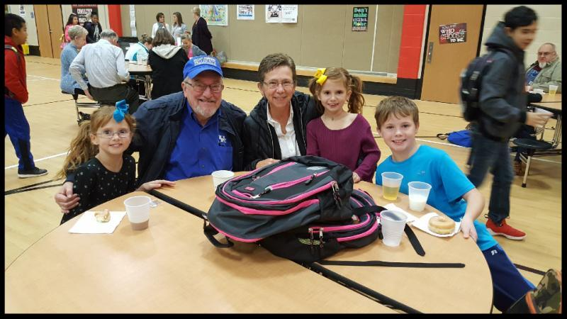Three students sit at a cafeteria table with their grandparents