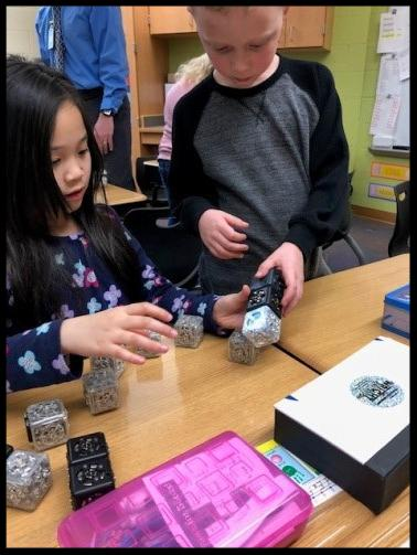 Two students work with palm-sized cubes. They appear to be linking them together into a line.