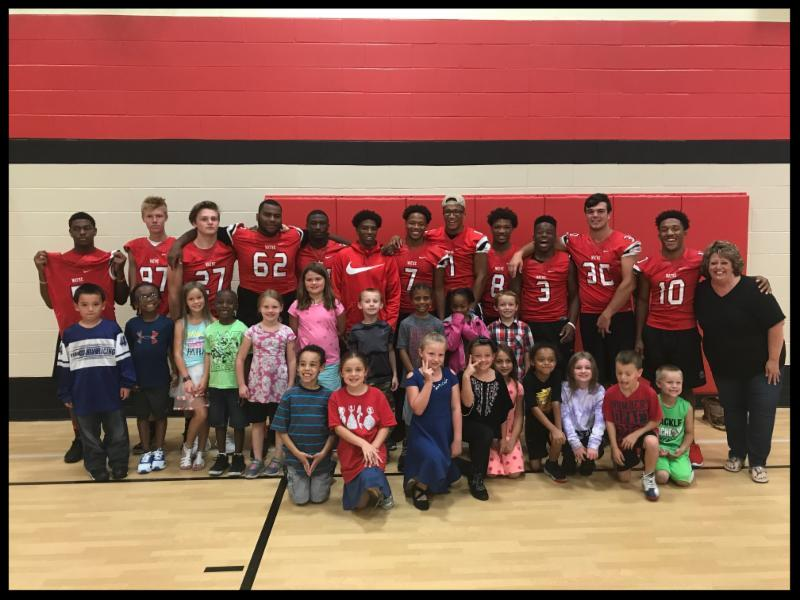 The picture was taken in a gymnasium. A line of football players in their jerseys stand behind a group of smiling elementary school students.
