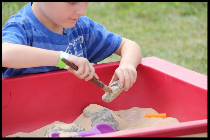 Child brushing sand off of an object he pulled from a sand table