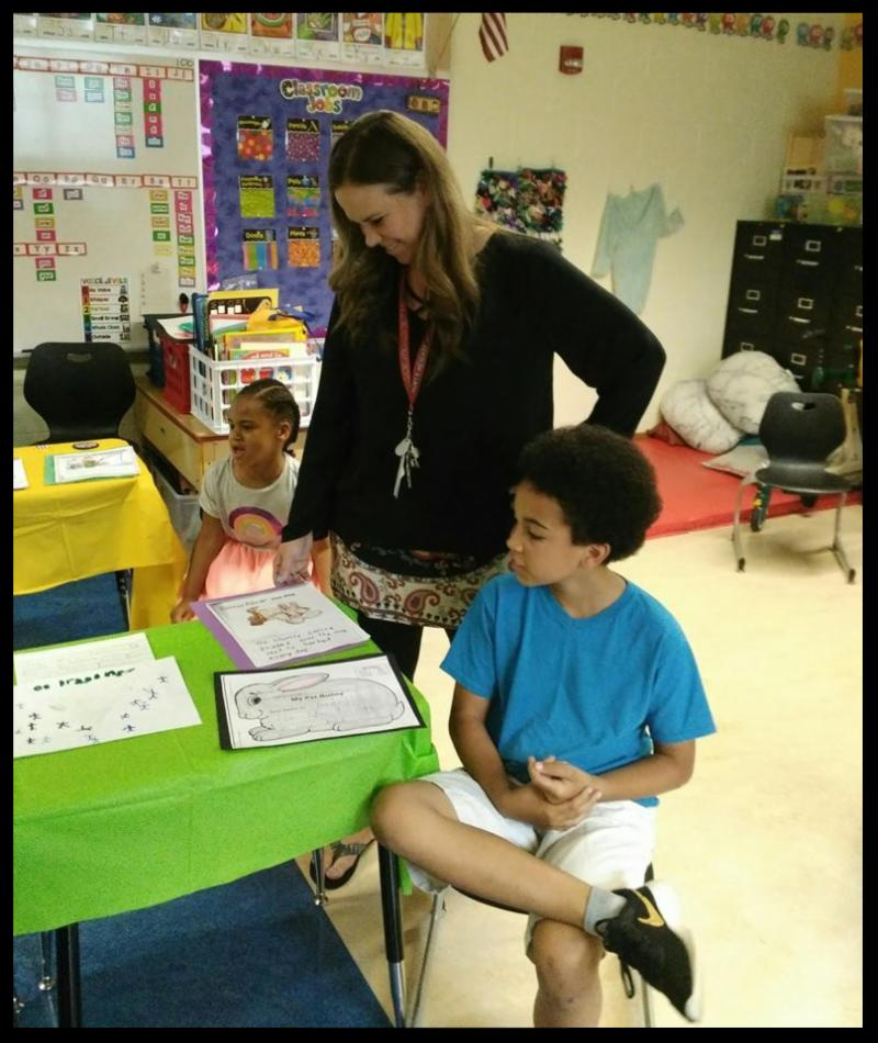 A teacher stands next to two students. She is looking down at a table that has artwork on it