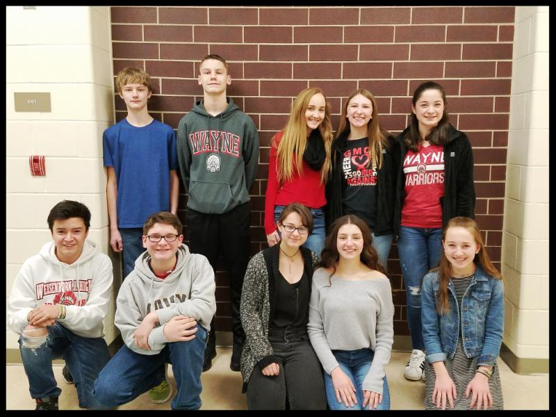 Ten students are lined up in two rows against a brick wall. They are smiling at the camera.