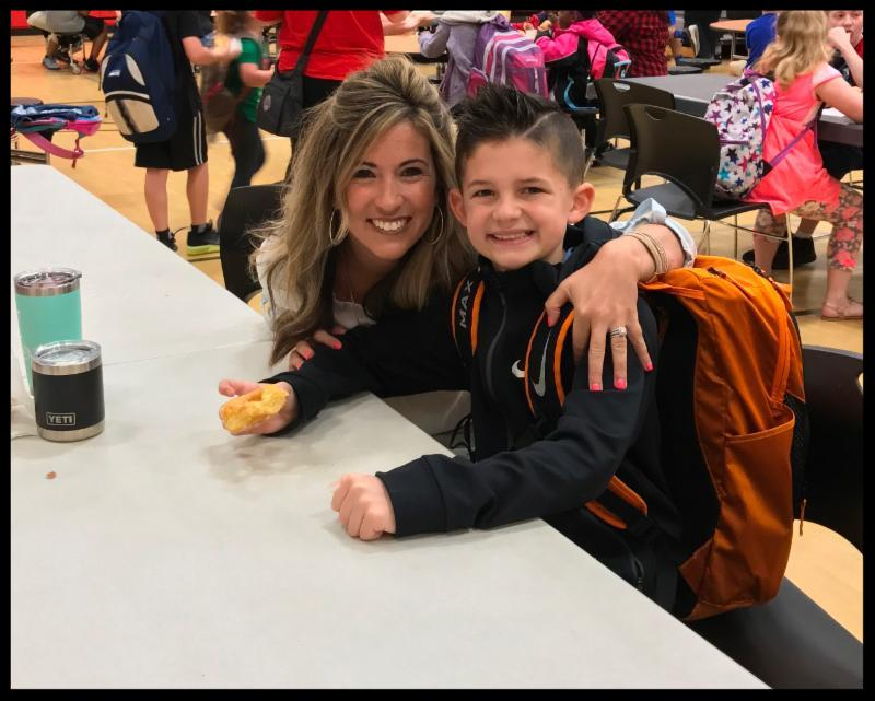 A woman sits at a cafeteria table. She has her arm around the shoulders of her son_ who is holding a doughnut. Both are looking at the camera and smiling