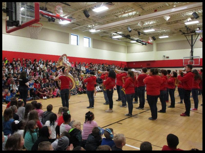 The image shows the backs of band students performing in the Rushmore gym_ which is packed with students.