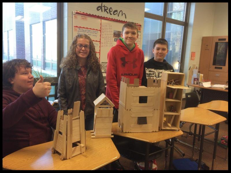 Four students stand behind a display of fortress-like buildings made out of popsicle sticks