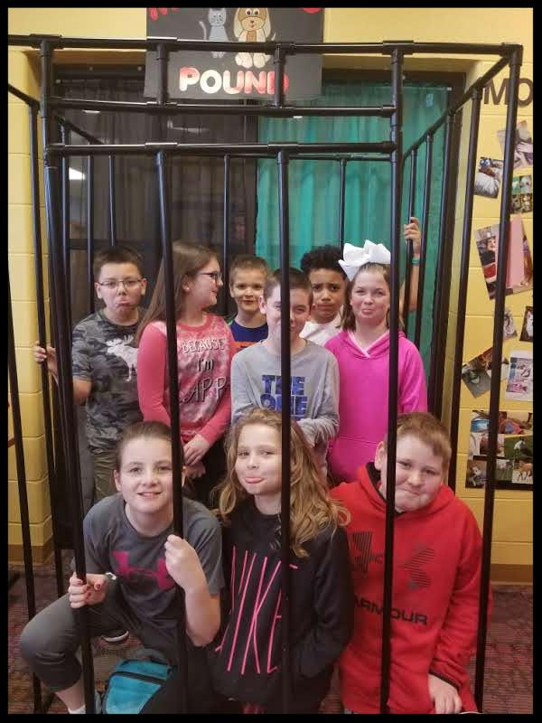A group of students are inside a large cage. A sign on top reads Monticello pound. The students are making varying sad faces or smiling.