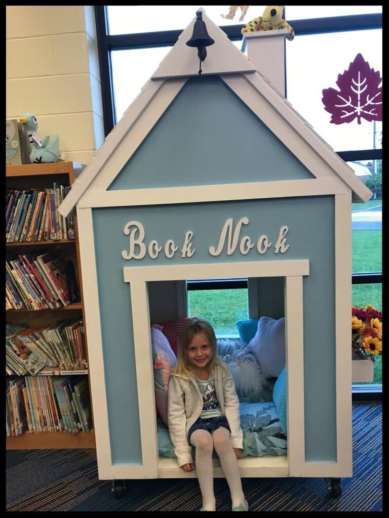 A young girl sits inside a little house-shaped building. It is blue with white trim. It says Book Nook on the outside of it. It is in a library_ there is a shelf of books next to it.