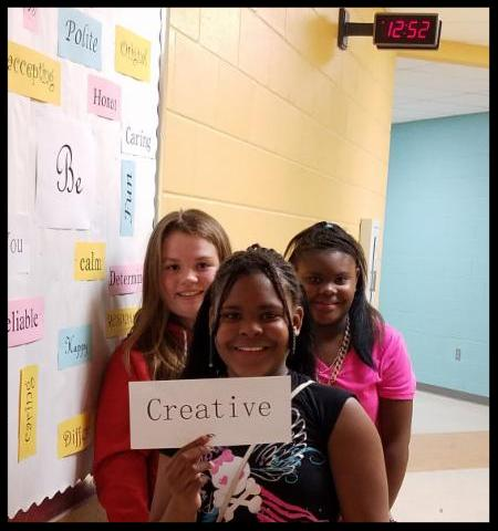 Three students stand in a group_ one holding a sign that says creative.
