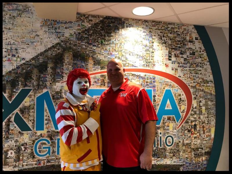 Principal Berk_ wearing a red shirt_ is standing next to Ronald McDonald.
