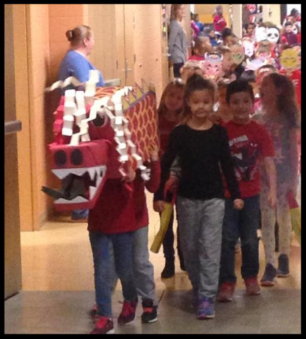 A parade of students walks down a hall. The student in front has a large dragon head on_ it appears to be a box covered in decoration_ with another box for a snout with sharp teeth and a tongue coming out.