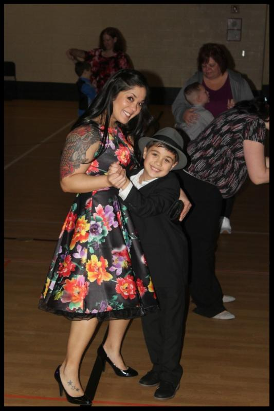 A woman and her son are dancing and smiling at the camera. The woman is wearing a dress_ her son has on a suit and a hat. They look happy.