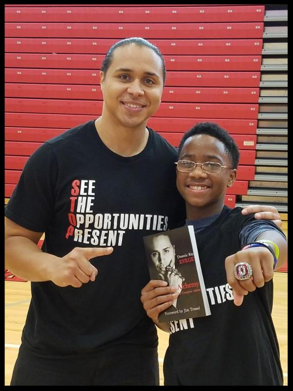 Donnie Evege has his arm around a student. Both are looking at the camera and smiling. The student is holding a copy of a book by Evege and is showing off an bejeweled ring in the shape of an O on his finger.