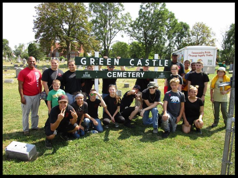 A group of students gathered around a sign that reads Green Castle Cemetery