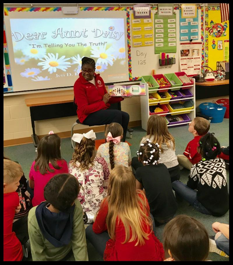 Ms. Dokes sits in front of a class of students. She is holding a book open so the students can see the illustrations. On the Smart Board behind her an image of the book jacket is projected. It is a picture of daisies and the words Dear Aunt Daisy I_m Telling You the Truth_