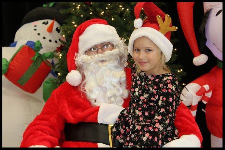 A young girl wearing a santa hat sits on Santa_s lap. Both are looking at the camera.