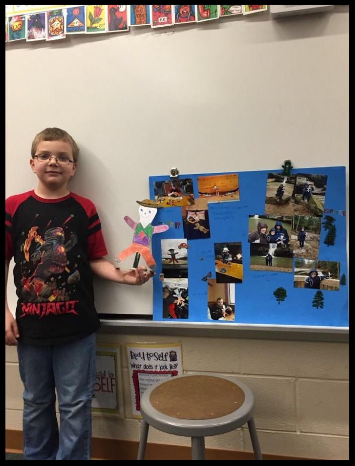 Student holding a picture of flat stanley