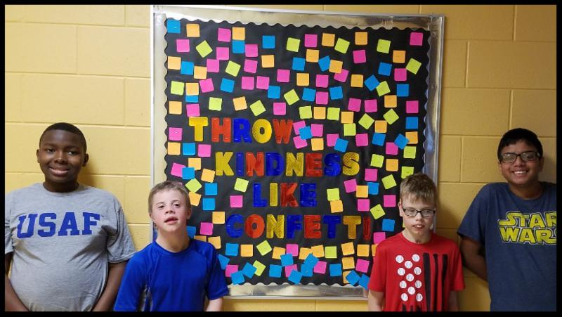 Four students stand in front of a bulletin board that says throw kindness like confetti. Scattered around the words are post-its in different colors.