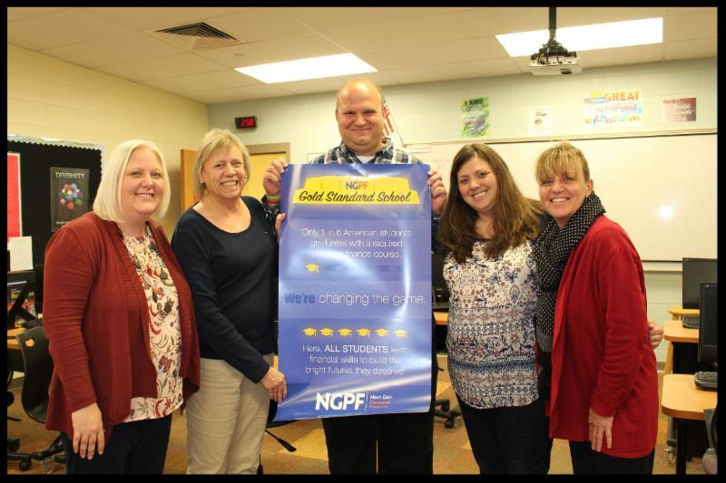 Principal Berk stands with four teachers. He holds a poster from NGPF declaring Wayne is a gold standard school