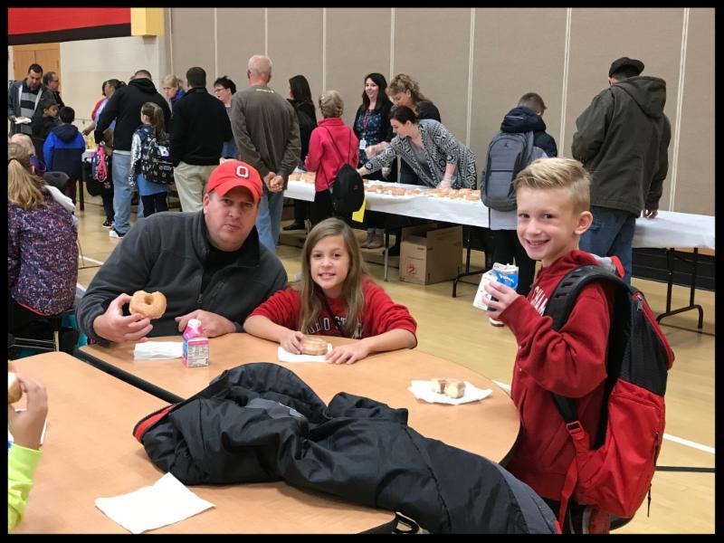 A dad and his daughter and son smile at the camera. They are sititng at a cafeteria table. The dad has a doughnut in his hand_ and the son is holding a carton of milk.