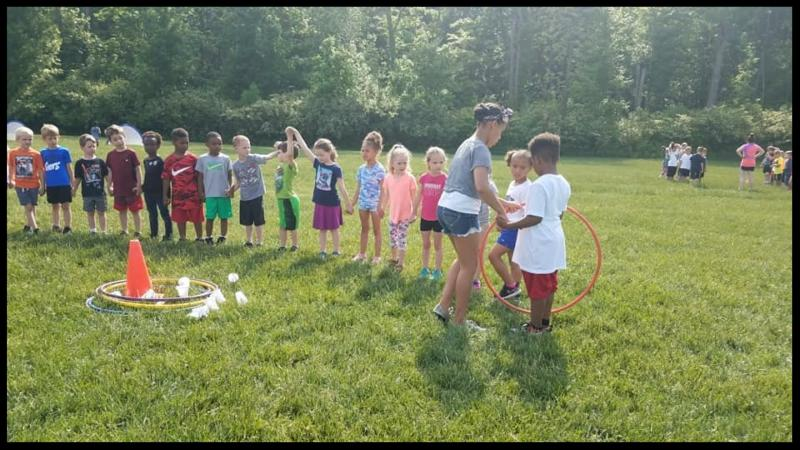 Students stand in a line in a grassy field. A sixth grader is handing a hula hoop to a student in the line