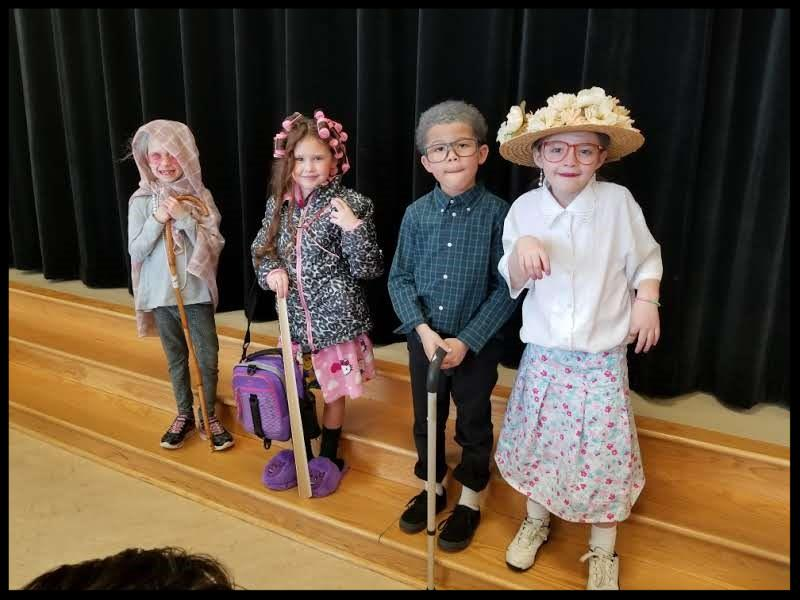 Four students stand in a row. They are dressed like they are old_ one has a kerchief on her head and is holding a cane_ another little girl has rollers in her hair and is wearing slippers_ a boy has gray hair_ big glasses_ a button-up shirt and a cane_ and a fourth girl has on a big hat with flowers on it_ big glasses_ and a big blouse and skirt.