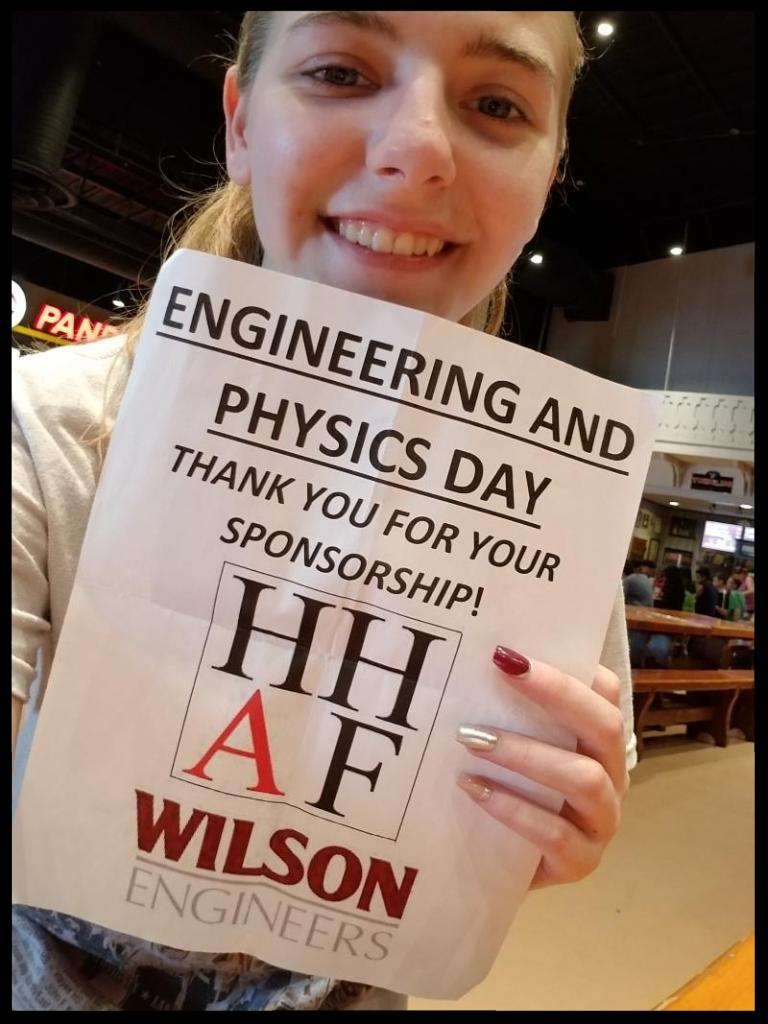 A student is holding  a piece of paper that says Engineering and Physics Day Thank you for your Sponsorship_ HHAF and Wilson Engineers