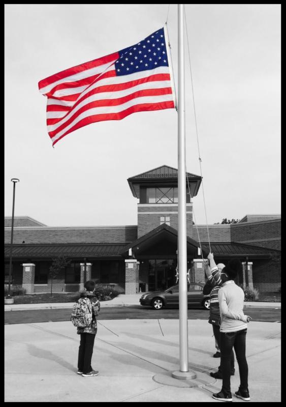 Image shows students standing outside of the school lowering the flag.