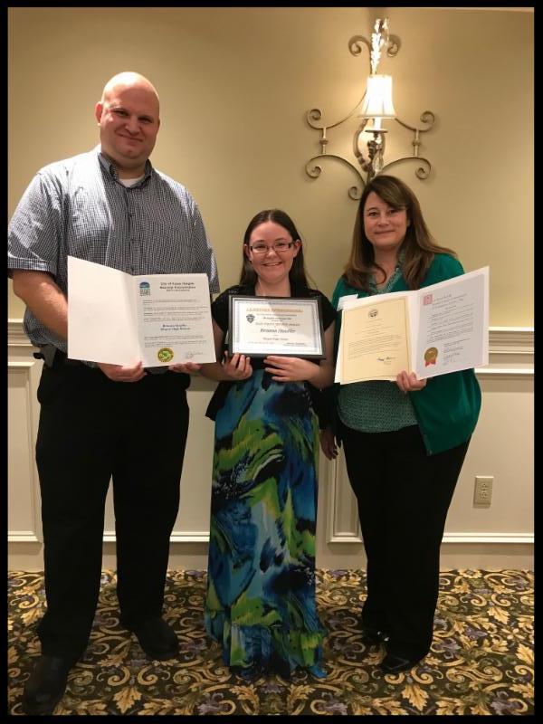 Mr. Berk_ Mrs. Davis_ and Brianna Stauffer stand in a row. They are holding certificates and smiling.