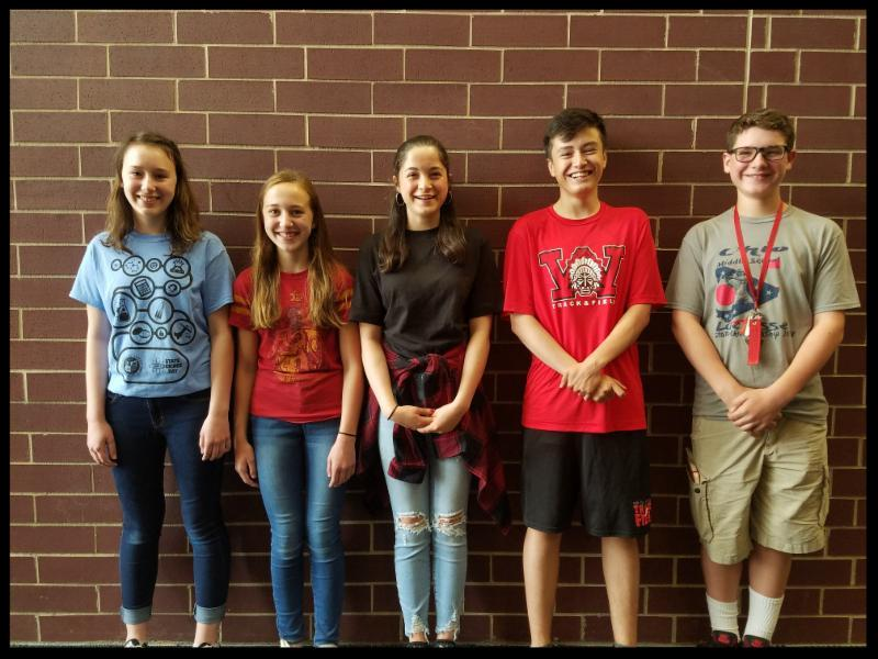Five students stand in a row against a wall. They are looking at the camera and smiling.