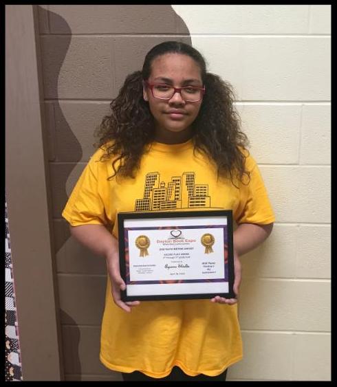 A student holds a framed certificate naming her as an award recipient