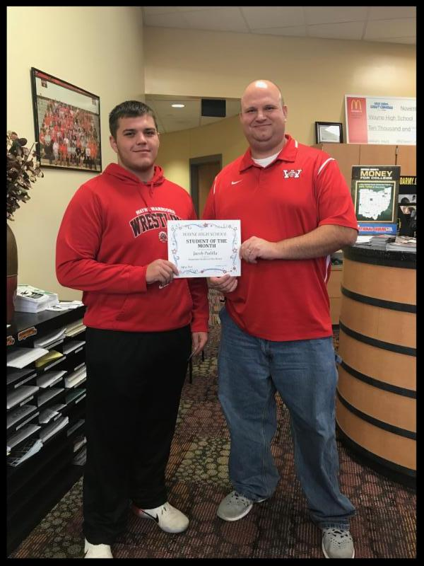 Jacob stands next to principal Berk. They are both holding a student of the month certificate