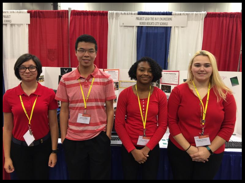 Four students all wearing red shirts stand in a line and smile at the camera