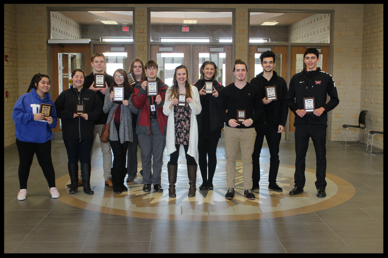 Eleven students stand in a line holding up plaques