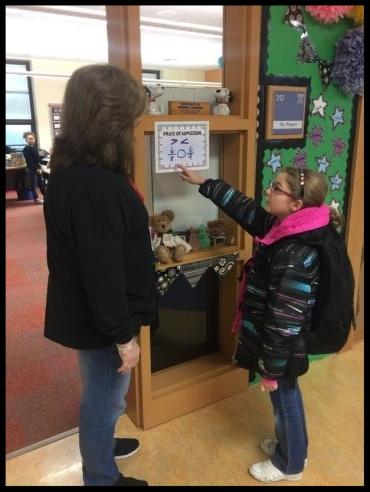 A student and a teacher stand at a classroom door. The student is pointing at a math problem hanging on a piece of paper next to the door. It appears to be a greater than_less than problem