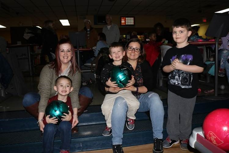 Two adult women sit on a set of stairs. The women each have a child on their lap holding a bowling ball. Another young boy stands to one side.