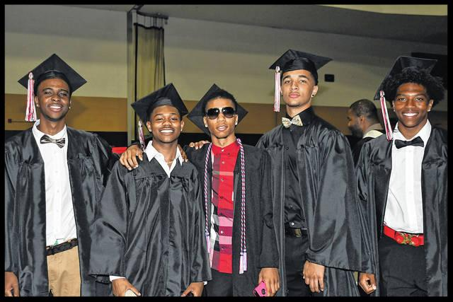 Five boys stand in a row in their graduation robes and hats