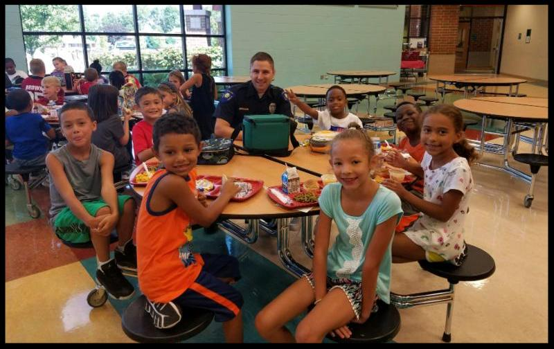 Officer Lambert sits at a round table with students who are facing the camera and smiling