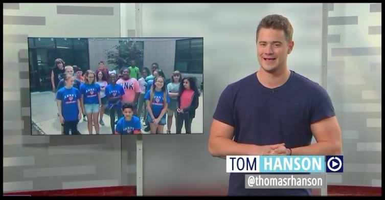 Image of a television screen. Newscaster Tom Hanson appears to be talking_ while over his shoulder is a screenshot of students from Valley Forge.