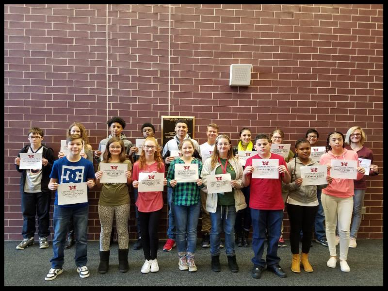 18 students stand in two rows in front of a brick wall. They are smiling and holding up certificates