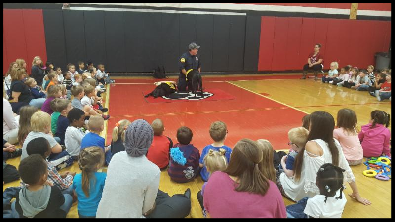 Students sit in a _U_ around fireman Jeff and two black dogs. One dog is lying on the floor and the other is standing in front of fireman Jeff.