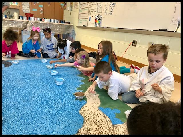 Students are sitting and lying down in front of a large piece of paper that has blue_ brown and green dots on it. They are in different stages of dipping their brushes in paint and of painting.