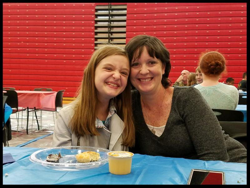 A woman and a student sit at a table and smile at the camera