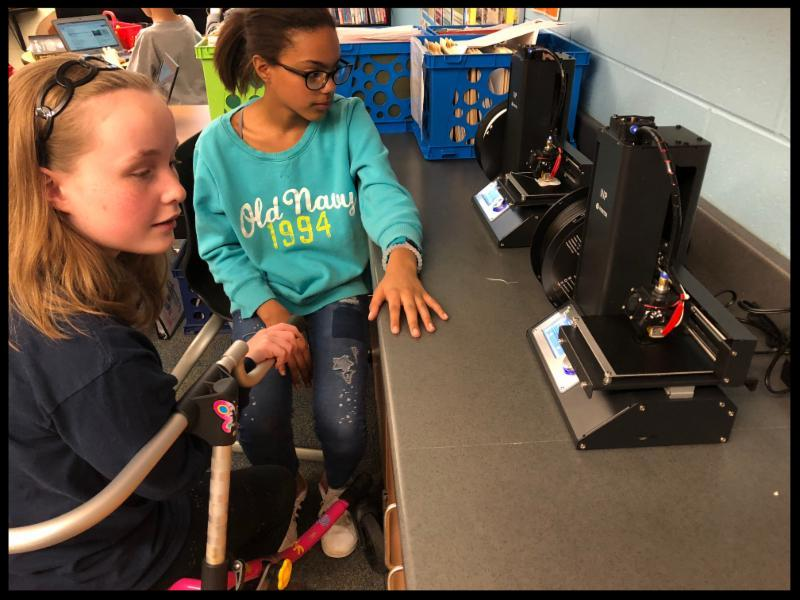 Two girls sit in chairs next to a long counter. They are looking at two 3D printers on the counter.