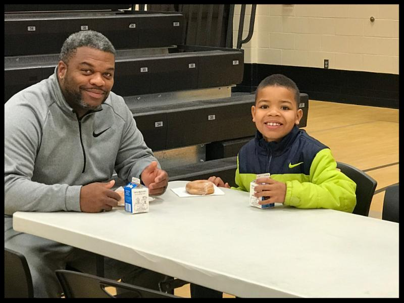 A dad and his son smile at the camera. There are doughnuts on the table in front of them_ and the son has his hand wrapped around a milk carton. They are both smiling.