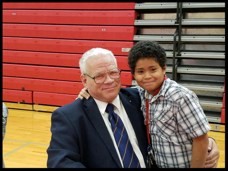 A young boy hugs an older man and they smile at the camera