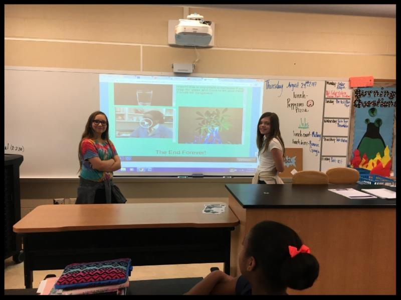 Two students stand in front of a smart board and that has an image from their presentation on it and smile at the camera