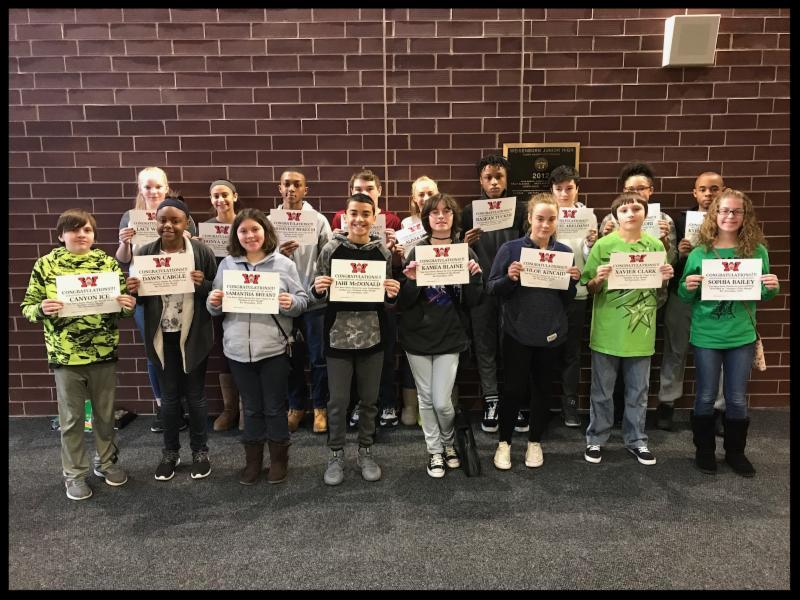 A group of 17 students stand in front of a wall_ they are smiling and holding up certificates