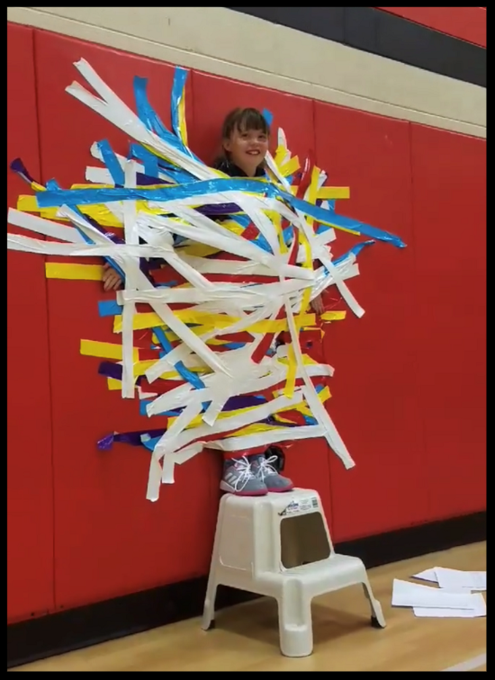 A girl is standing on a stool. She is taped to the wall in the gym with multiple colors of duct tape. She is smiling.