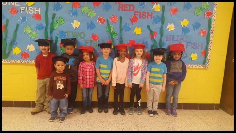 Nine preschool students stand in a line. They have mortarboards on their heads